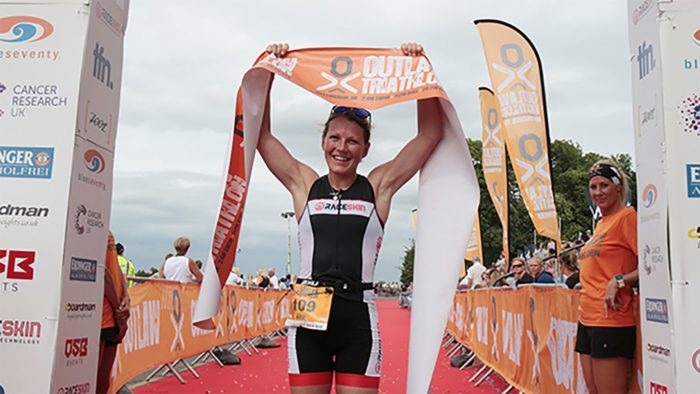 Ali Wilson crossing the line at Outlaw Triathlon